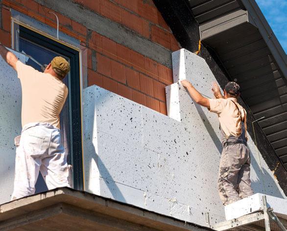 Arbeitende Mauerer sanieren die Außenwand eines Gebäudes / Symbolbild für den Ratgeber Sanieren und Energiesparen