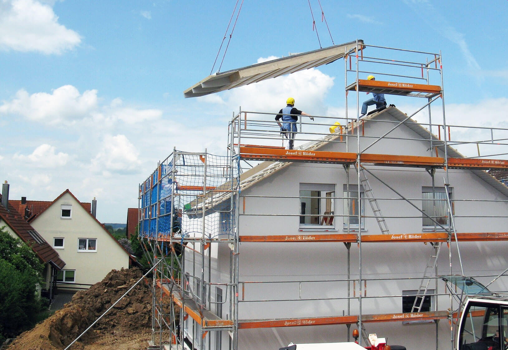 Kran setzt Dachschräge eines Neubaus ein / Symbolbild für neue vielseitige Dämmstoffe